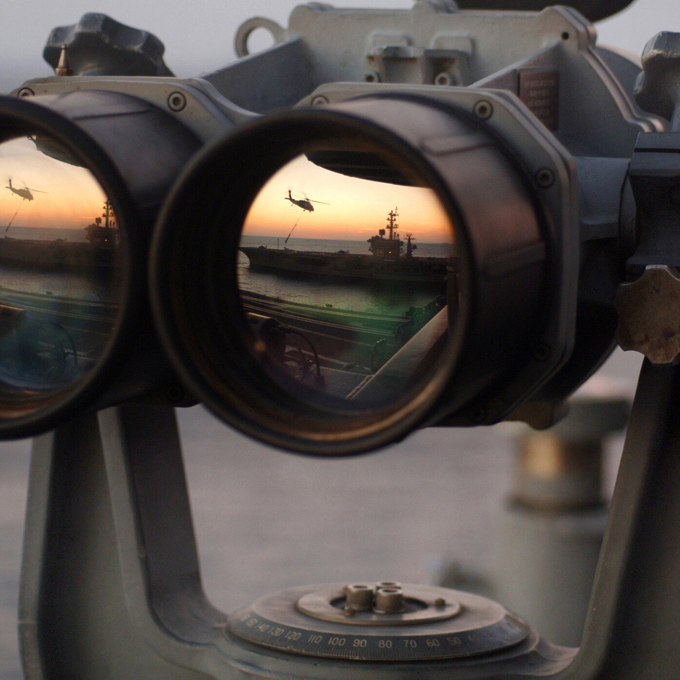 "051104-N-2984R-004 Onboard USS Harry S. Truman The sun sets over a set of ""Big Eyes"" binoculars on the signal bridge of the Nimitz-class aircraft carrier USS Harry S. Truman (CVN 75), while an MH-60 Knighthawk assigned to the ""Bay Raiders"" of Helicopter Combat Support Squadron (HSC) 28 airlifts several replenishment slings to USS Dwight D. Eisenhower (CVN 69).  USS Harry S. Truman is currently underway off the coast of the Eastern United States conducting replenishments at sea with USNS Arctic (T-AOE 8) and weapons offload operations with USS Enterprise (CVN 65) and USS Dwight D. Eisenhower (CVN 69). Harry S. Truman is scheduled to enter its Docked-Planned Incremental Availability at the beginning of 2006. US Navy photo by Photographer's Mate Airman Ricardo J. Reyes.  (Released by HST Public Affairs.)"